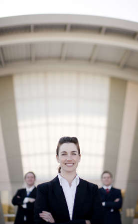 Businesswoman smiling standing in front of two businessmen with arms folded