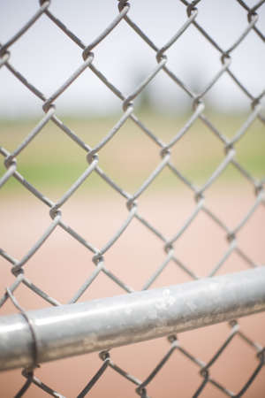 diamond background: Chain fence with baseball diamond in background