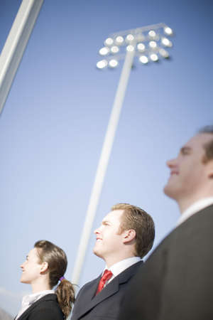 three happy business people standing and smiling with big lights behind in background Stock Photo - 3056826