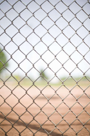 chain link fence pattern in front of a baseball field in the summer photo