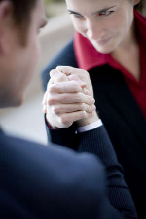 wrestle: businessman and businesswoman wearing suits sit as they arm wrestle Stock Photo