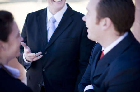 businesspeople in suits standing discussing with each other and smiling Stock Photo
