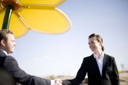 businessman and businesswoman standing and shaking hands in front of large yellow flower photo