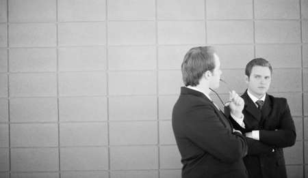 two businessmen in suits standing and talking with each other with brick background photo