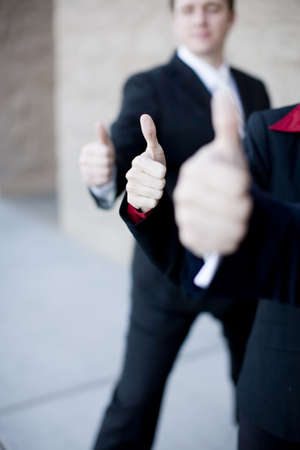 three businesspeople in a row standing giving thumbs up photo