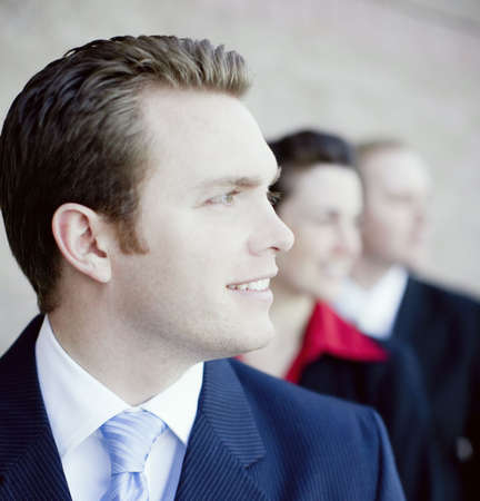 attractive businesspeople wearing formal clothing standing in a line looking in same direction and smiling photo
