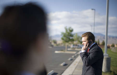 A businessman is talking on his cell phone wearing a dark suit standing outside with other business people looking at him