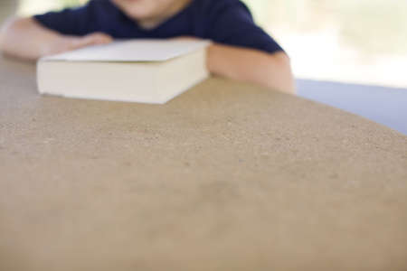 a child is sitting next to his book blurred in the background with a large section of a tan table in the foreground
