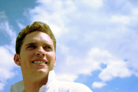 A young, happy man looks over his shoulder while wearing a white shirt with and with a big smile while standing under a blue sky full of clouds Imagens
