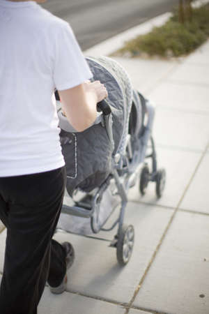 A mother wearing a white t-shirt is walking her babies on the sidewalk outside in a baby stroller