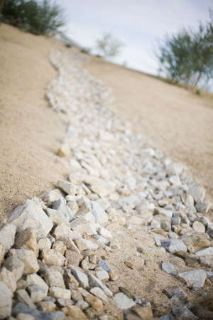 a rock path made of many different tan rocks and sand line a simple path down a hill  Imagens