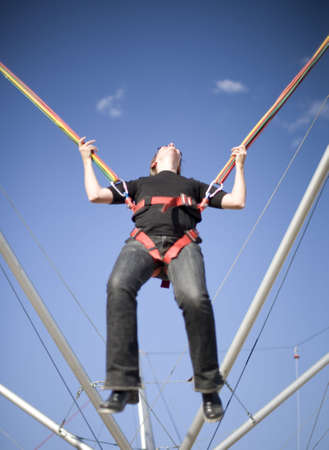 a woman is in a rope harness where shes jumping up into the sky with her head back laughing Imagens