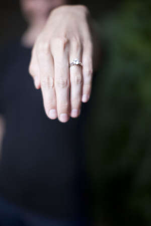 a woman holds her hand out and shows her diamond ring on her wedding finger