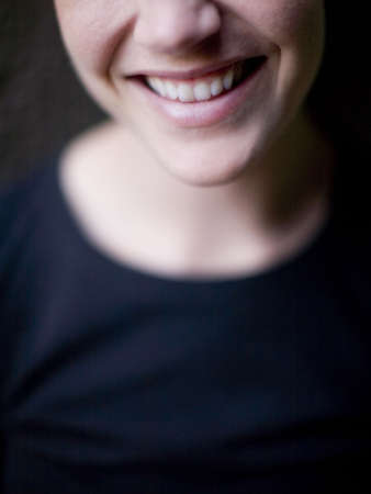 a woman is smiling with a big smile outside in natural light with a black shirt on  Imagens