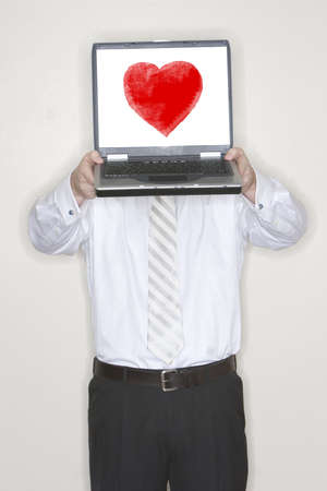 Businessman Holds a laptop above his head and presents it in his office with a valentines heart on his screen