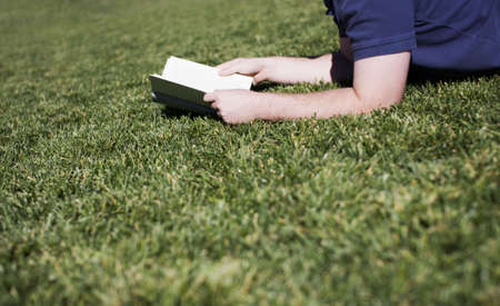 a man is reading his book in the grass in the sunlight while lying down on the grass