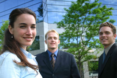 A group of three business people standing outside and smiling as they look ahead while standing in front of a business building on a clear sunny day Imagens