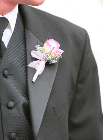A Groom stands ready for the wedding with his suit on and a flower on his suit