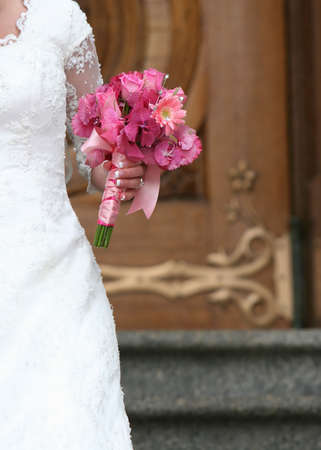 A Bride is walking down the steps in front of a door wearing her wedding dress and holding her flowers in her hand