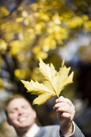 A man holds up a single leaf up into the air all alone as he looks ahead with a smile on his face and warmth on the autumn day Imagens