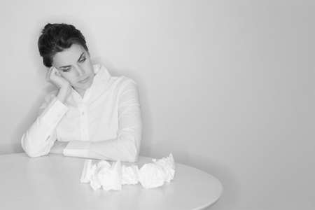 Business woman is frustrated with her work as she sits in her office at a table with a pile of paper