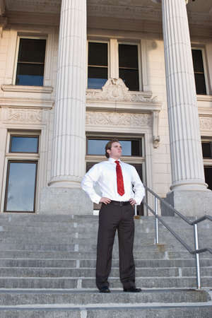 A businessman stands with his hands on his hips in front of the courthouse standing on the steps in front of the building