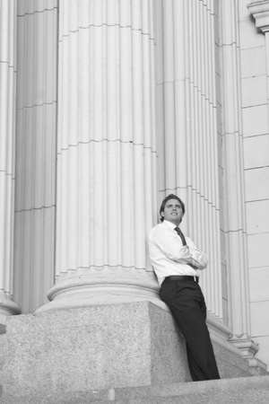 A businessman with his arms folded and standing against a column of a courthouse