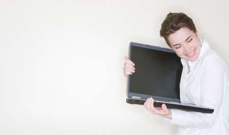 A beautiful businesswoman is hugging her laptop after getting some success in her job Imagens - 4202675