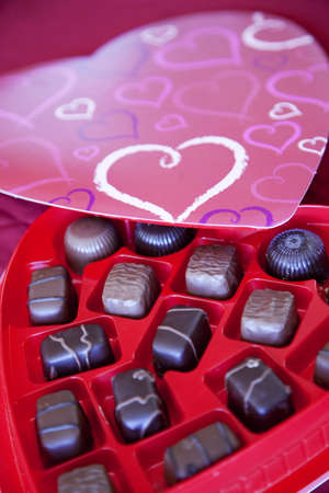 A box of chocolates is open with the top of the chocolate box on the outside rim of the pieces of chocolate