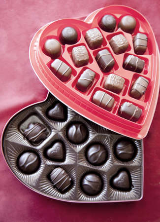 Two boxes of valentines day chocolates are together with the red box of chocolates on top of the dark box of chocolates on a red background Imagens