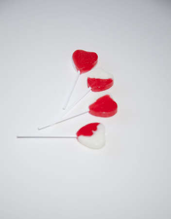 a group of valentine's day suckers are displayed on the white background together the suckers are red and white and shaped like hearts  Reklamní fotografie