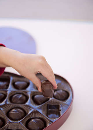 a girl is grabbing a piece of chocolate from a box of heart shaped chocolates