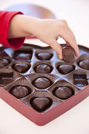 a girls hand is sneaking a piece of valentines day chocolate from a box of heart shaped chocolates  Imagens