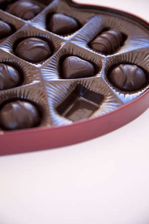 a big red box of chocolates in a heart shaped container with one of the chocolates missing