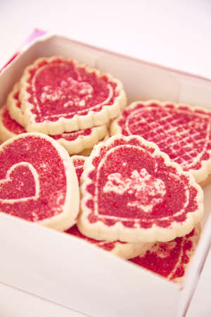 a box of valentines day cookies that are red and sprinkled stacked together