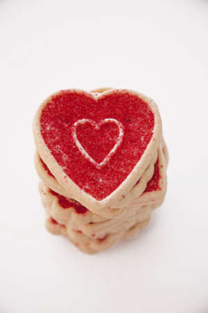 a stack of valentines day cookies with a heart shaped cookie at the top of the stack