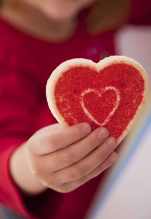 a girl is lifting up her valentines day cookie and holding the red cookie  Imagens