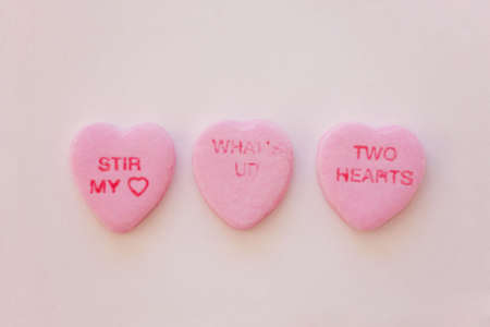 three candy hearts are grouped together in a row with little sayings on the hearts