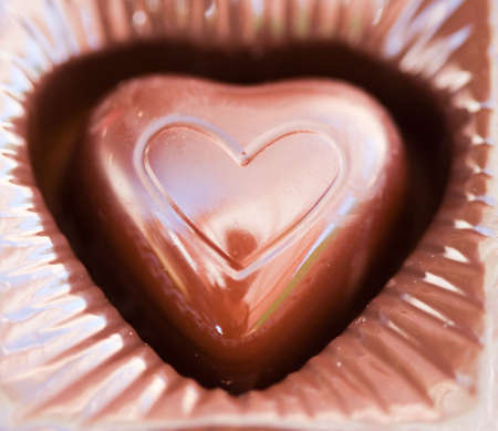 a close-up of a piece of chocolate with a heart shaped symbol stamped on the chocolate