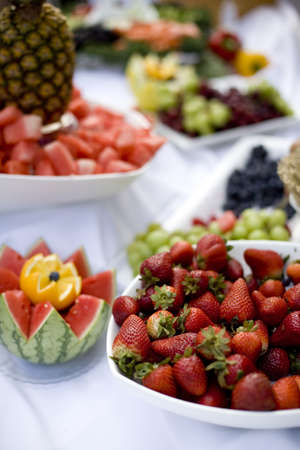 A table of food with strawberries, grapes, pineapple, watermellon, and an orange in the foreground.