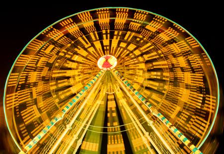 fairground: ferris wheel spinning at fairground at night