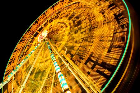 fairground: ferris wheel spinning at fairground in dark light