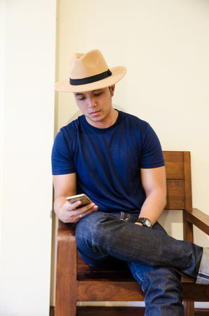 asian wear blue T-shirt siiting on wooden chair holding smartphone