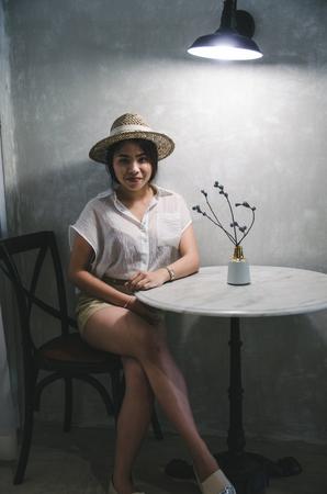asian women sitting in living room with dark light Imagens