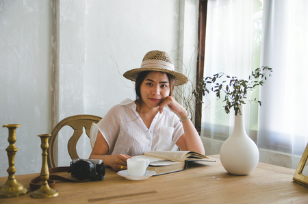 smiling asian women reading book on wooden table
