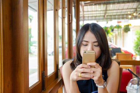 asian woman holding smartphone  at coffee cafe