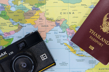 thai passport with black camera lay on asia map