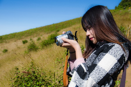 women traveller take a photo with digital camera on yellow grass background