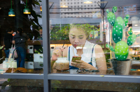 asian girl is looking smartphone in cafe