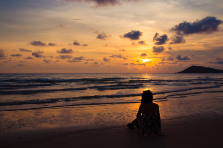 silhouette of girl sitting on beach with sunset Imagens